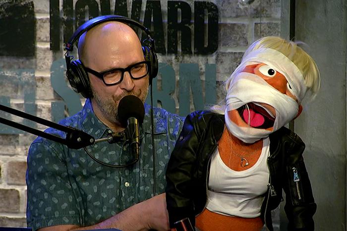 Stern Show staffer Shuli Egar shows off a newly-bandaged Tan Mom puppet.