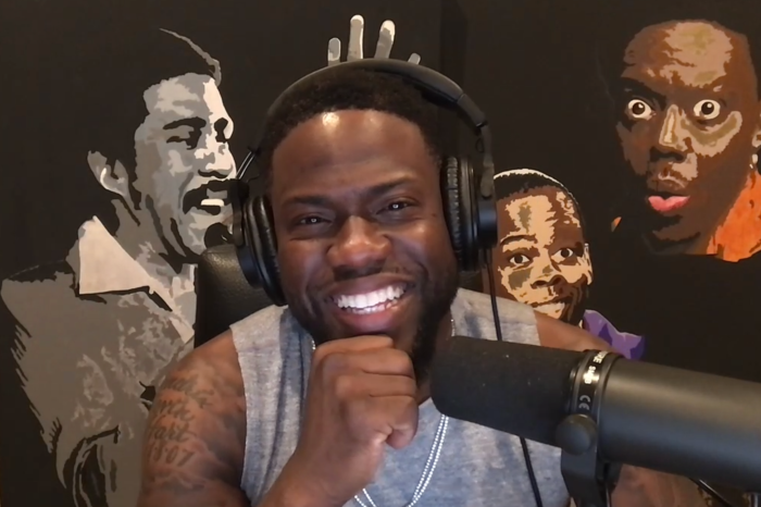 Kevin Hart at home with a mural behind him of fellow comedy legends Richard Pryor, Chris Rock, and Bernie Mac